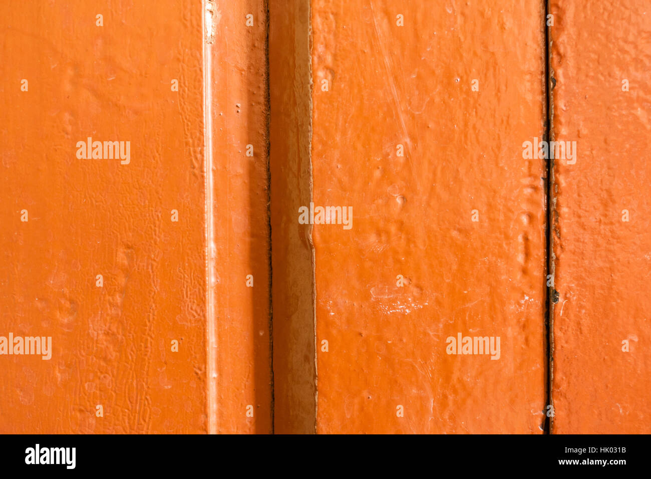 Old worn out wooden planks painted orange brown. - Stock Image