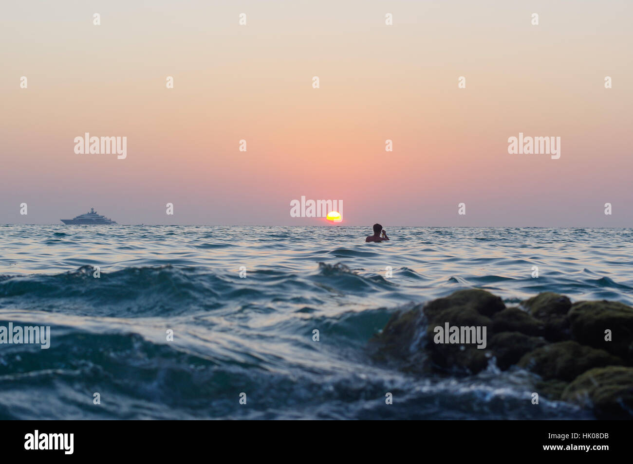 sea wave closeup at sunset time with red and orange sun reflection on the water. nature abstract blurred background. - Stock Image