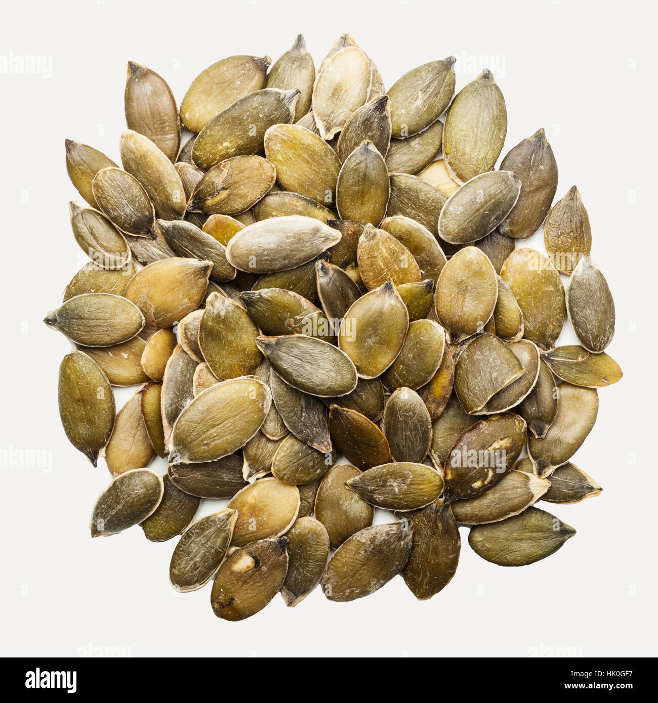 Pumpkin seeds on a white background - Stock Image