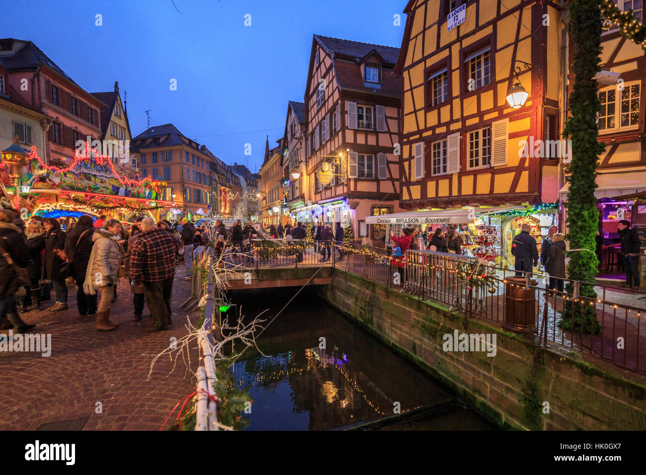 Tourists shopping at the Christmas Markets in the old medieval town of Colmar, Haut-Rhin department, Alsace, France - Stock Image