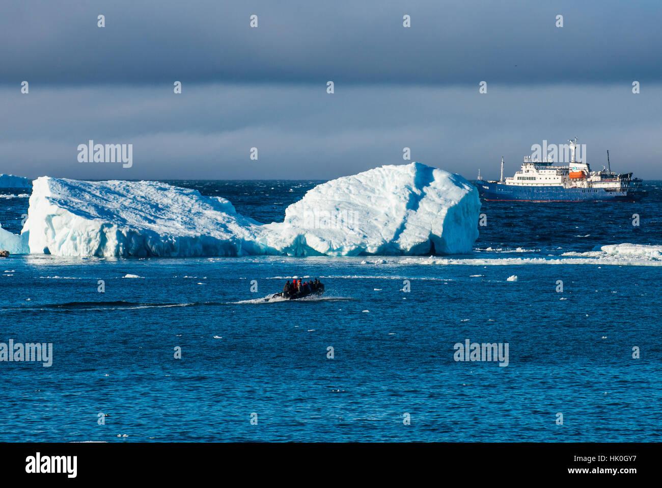 Zodiac cruising back to a cruise ship anchoring behind an iceberg, Brown Bluff, Antarctica, Polar Regions - Stock Image