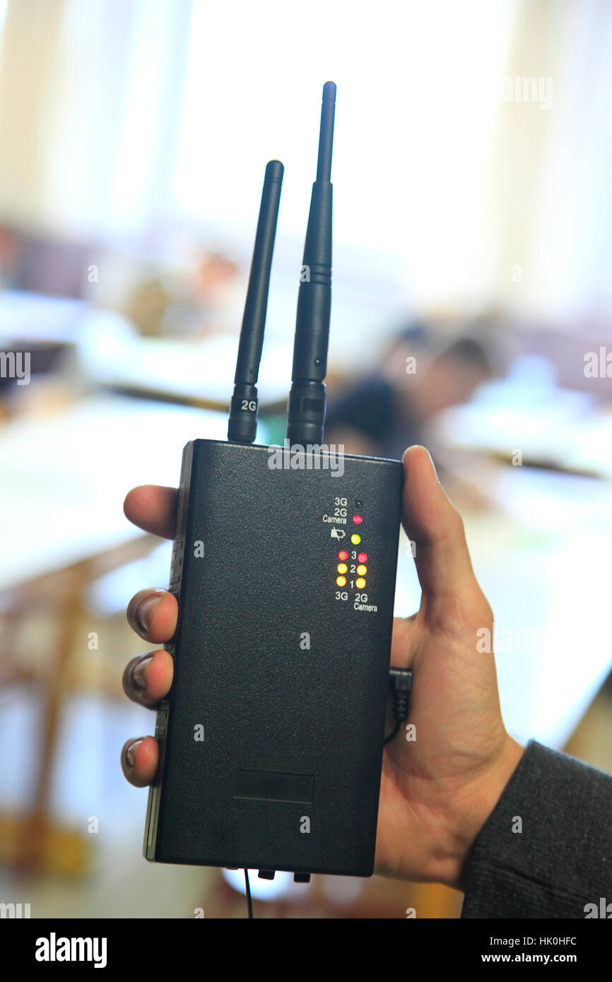 Room of examination for A Levels, closeup of a hand holding a mobile phones detector - Stock Image