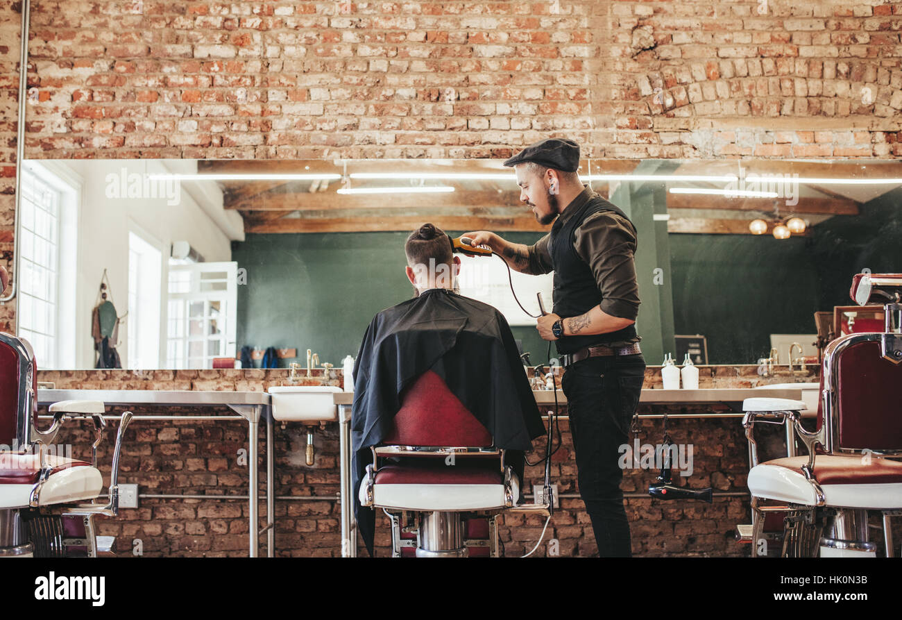 Hairstylist cutting hair of male customer at barber shop. Barber serving client, making haircut using hair clipper. - Stock Image