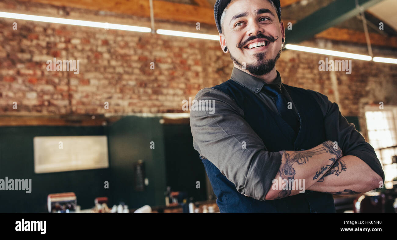 Close up of happy young male barber with cap looking away and smiling. Handsome hairdresser in salon. - Stock Image