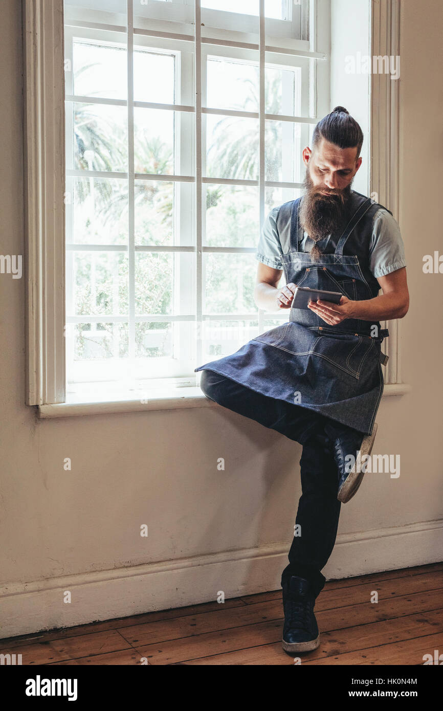 Hairdresser with digital tablet sitting on window sill of salon. Beard man using digital tablet at barbershop. - Stock Image