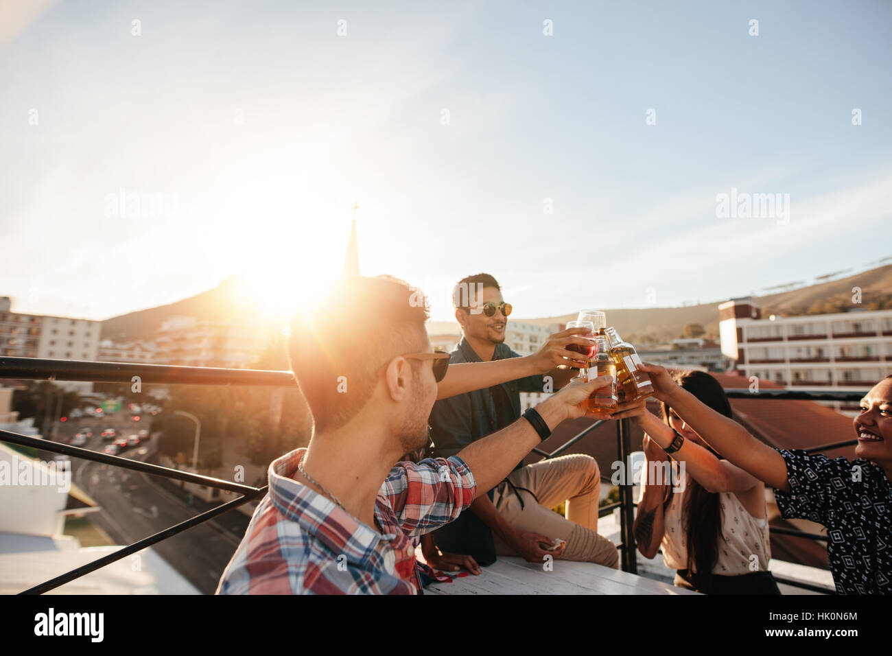 Friends toasting drinks at a party. Young friends hanging out at rooftop party and enjoying drinks. - Stock Image