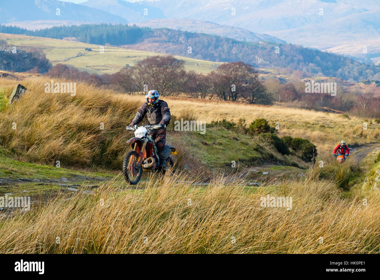 Men riding a dirt bike on a multi-use track through countryside in Snowdonia National Park. Capel Curig, Conwy, - Stock Image
