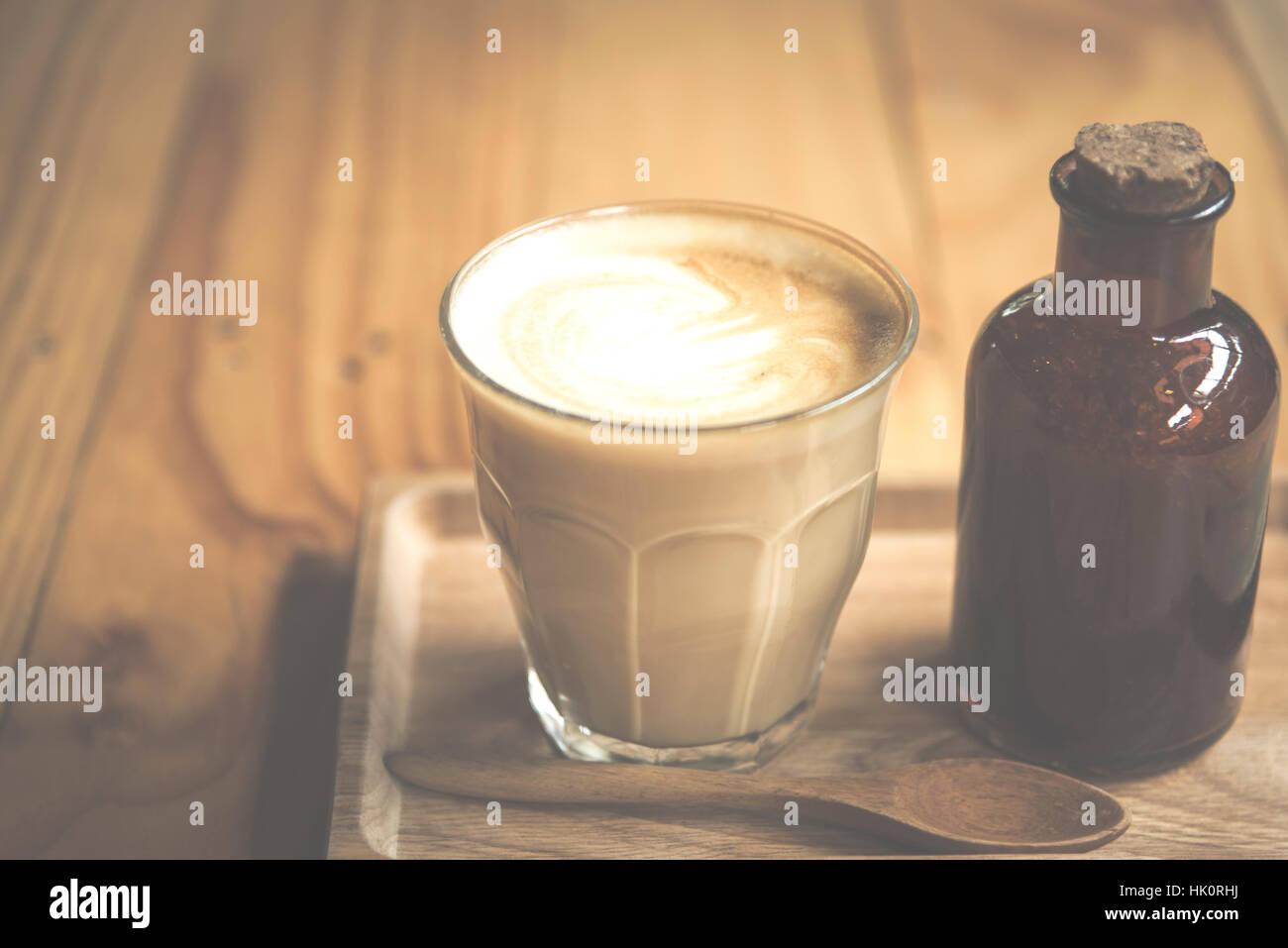 vintage art filter image of coffee latte art in cafe - Stock Image