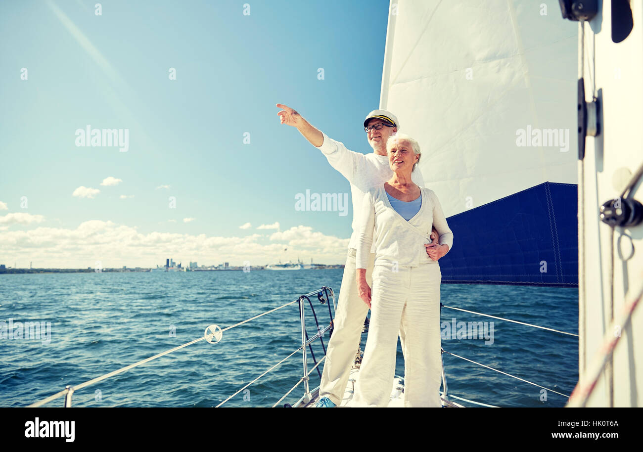 senior couple sailing on boat or yacht in sea - Stock Image