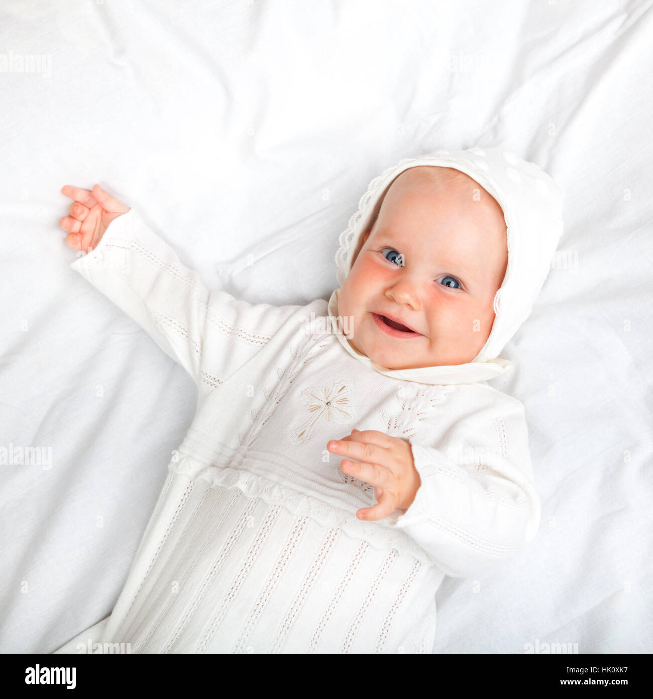 Close-up shot of six month baby girl wearing white christening clothes laying on a bed smiling - Stock Image