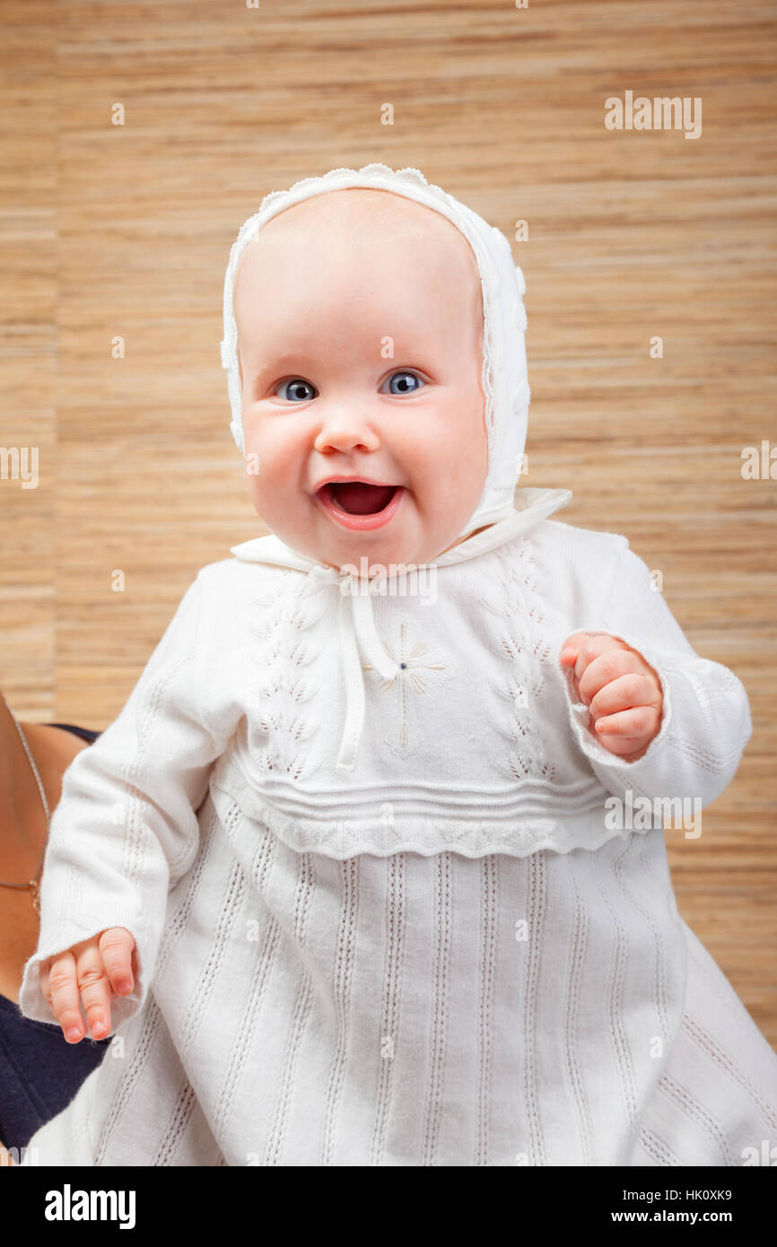 Cheerful six month baby girl wearing white christening clothes - Stock Image