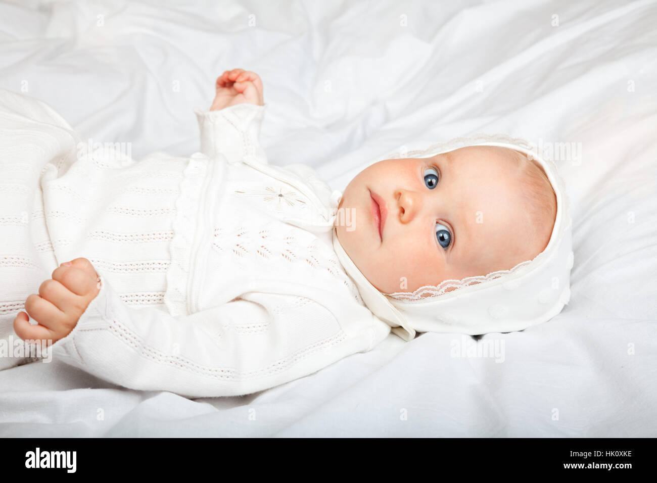 Close-up shot of six month baby girl wearing white christening clothes laying on a bed - Stock Image