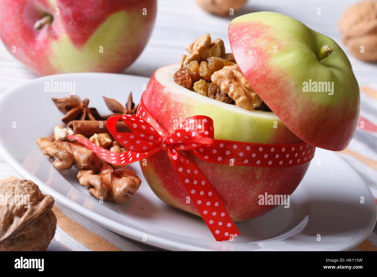 Red apple stuffed with nuts and raisins on white plate close up horizontal - Stock Image