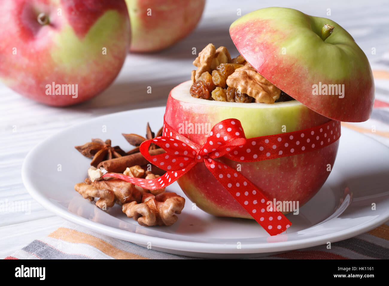 Fresh red apple stuffed with nuts and raisins on a white plate on the table horizontal close-up - Stock Image