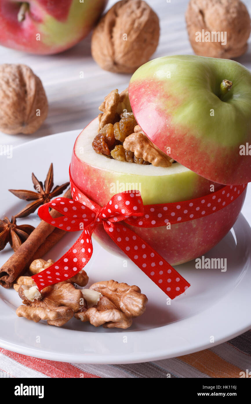 Fresh red apple stuffed with nuts and raisins on a white plate on the table close up vertical - Stock Image