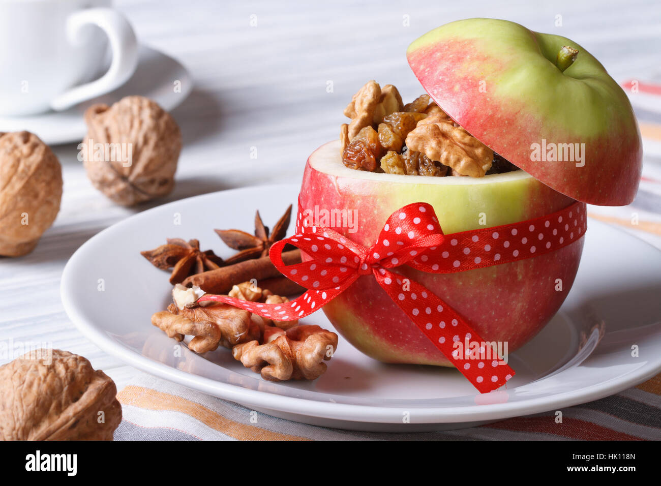 Red apple with nuts and raisins on a white plate and coffee on the table. Horizontal close-up - Stock Image