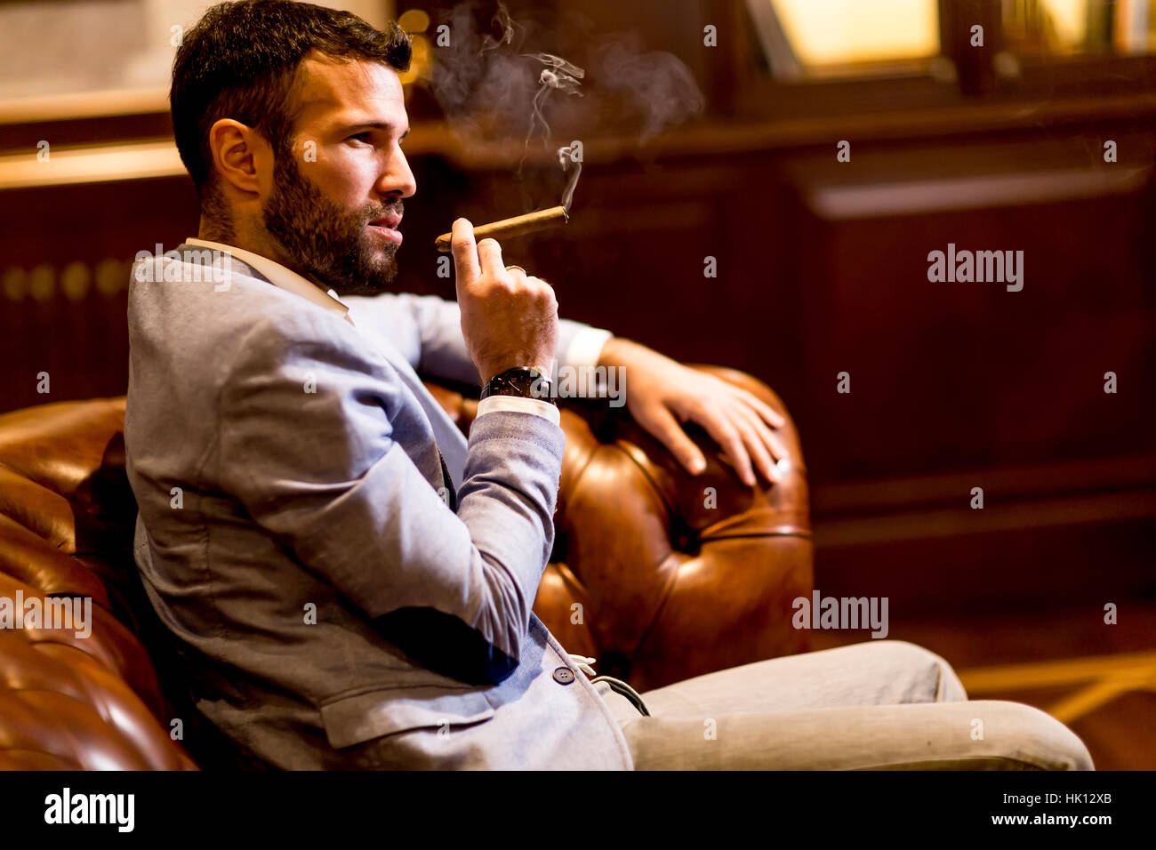 Handsome Man Sitting On A Leather Sofa And Smoking Cigar