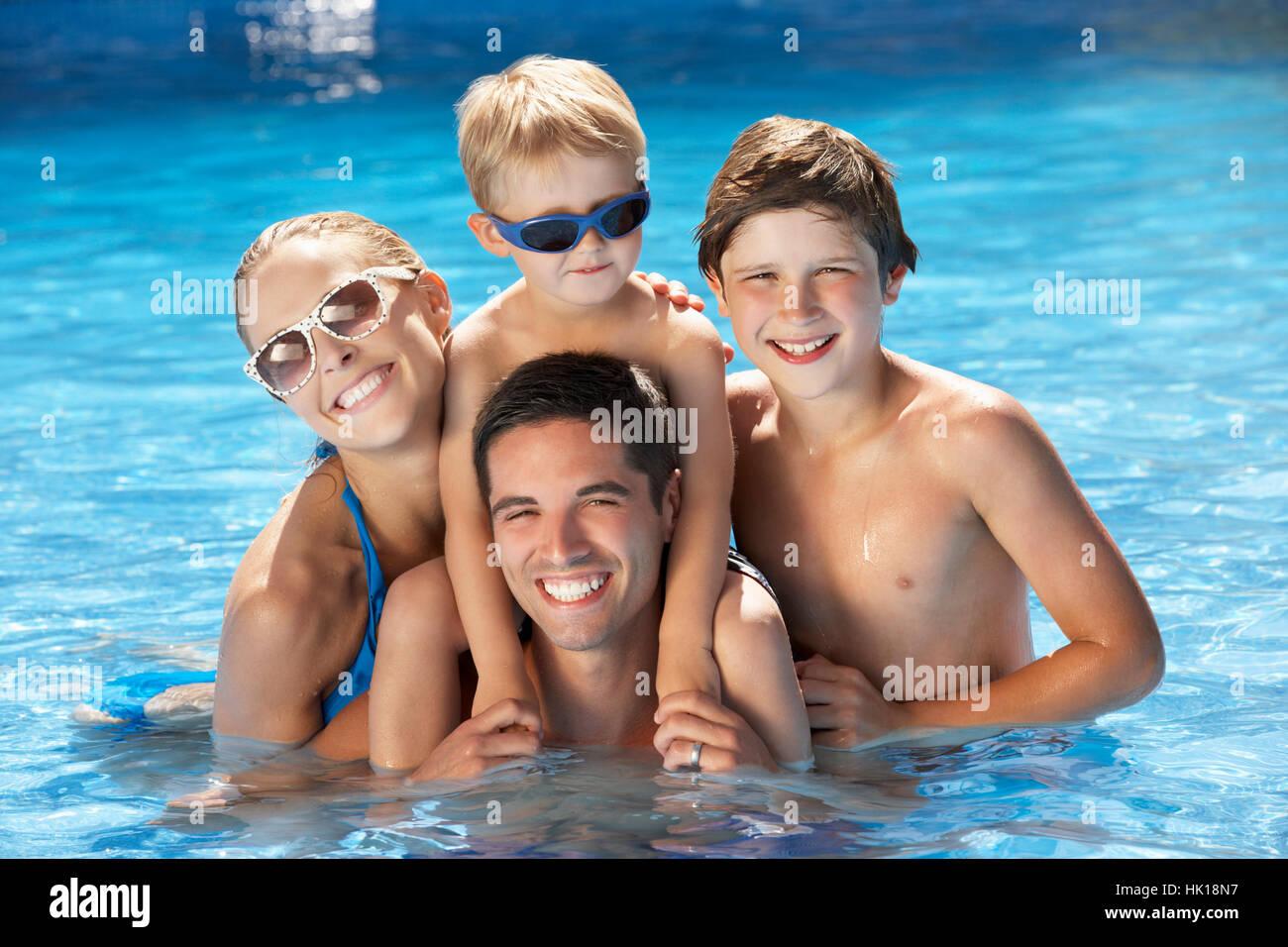 Family Having Fun In Swimming Pool Stock Photo