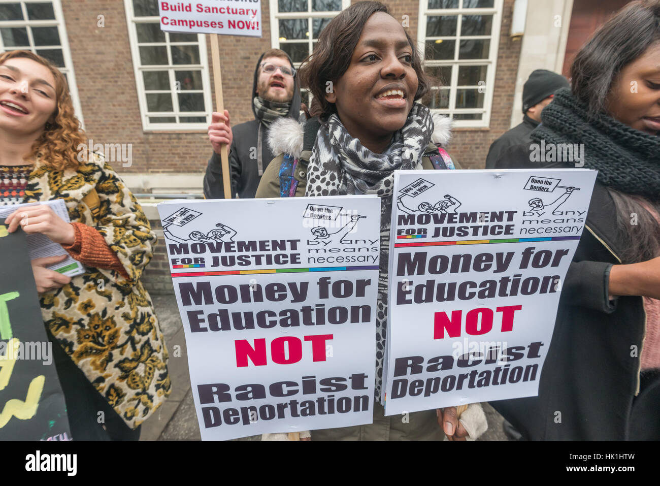 London, UK. 25th January 2017. A woman holds two placards as Movement for Justice and NUS London protest outside Stock Photo