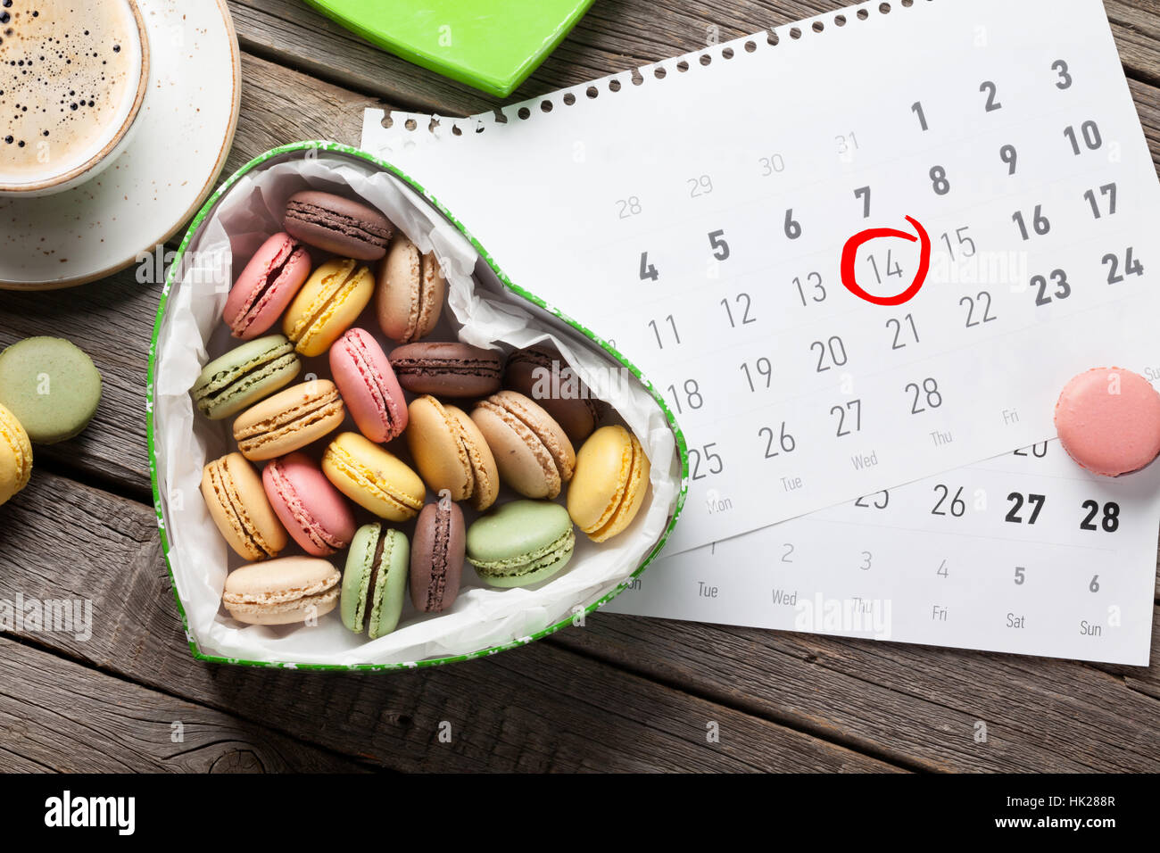 Valentines day greeting card. Macaroons in heart shaped gift box and coffee cup over february calendar. Top view - Stock Image