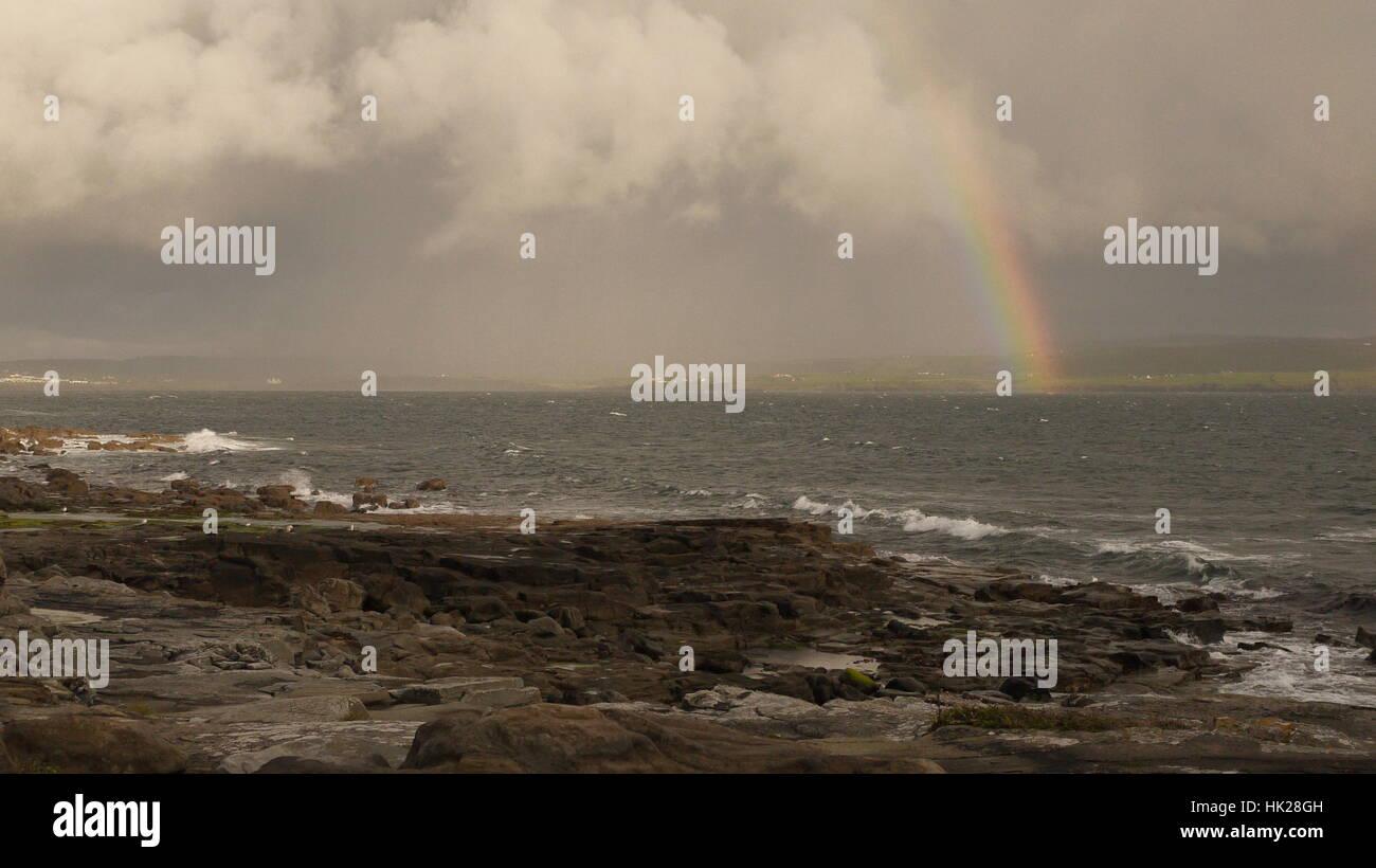 A rainbow and a storm cloud off the Irish coast - Stock Image