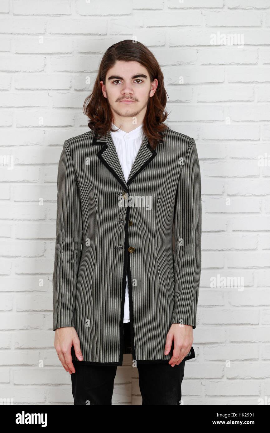 Confident handsome male model  with long hair. fashion photography, fashion editorial concept - Stock Image