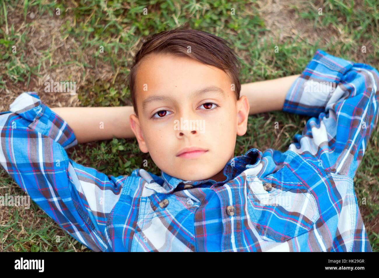 Tween boy looking up into sky with hands behind head - Stock Image