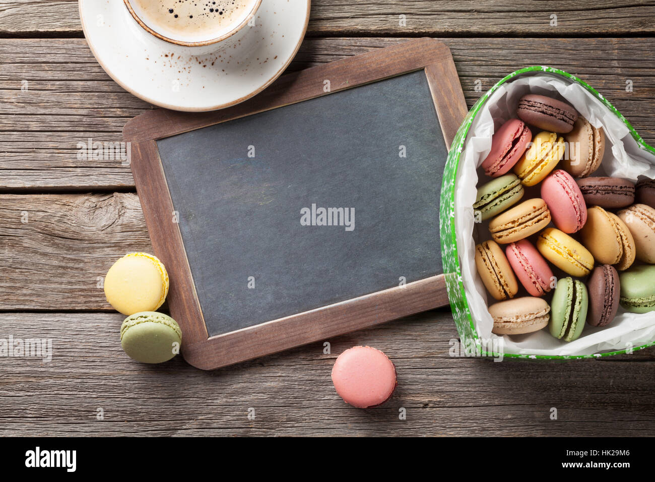 Colorful macaroons in Valentines day heart shaped gift box and coffee cup on wooden table. Top view with chalkboard - Stock Image