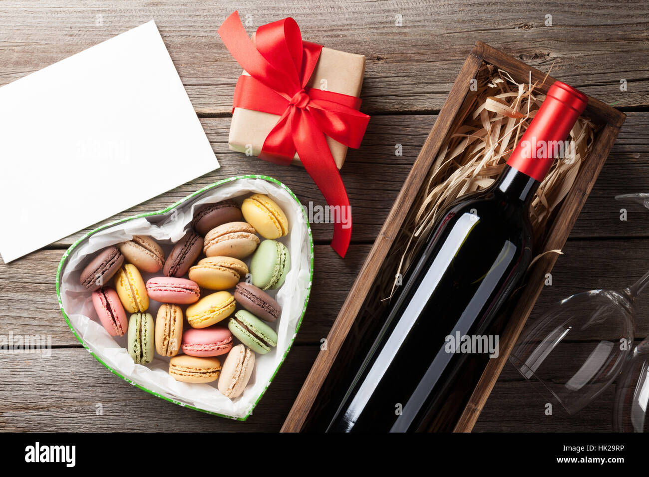 Valentines day greeting card. Red wine, macaroons gift box and glasses on wooden table. Top view with space for - Stock Image
