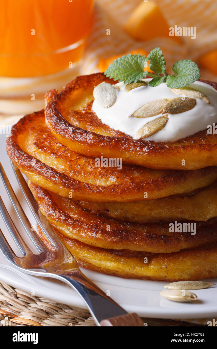 Delicious pumpkin pancakes with sour cream close-up on the table. vertical Stock Photo