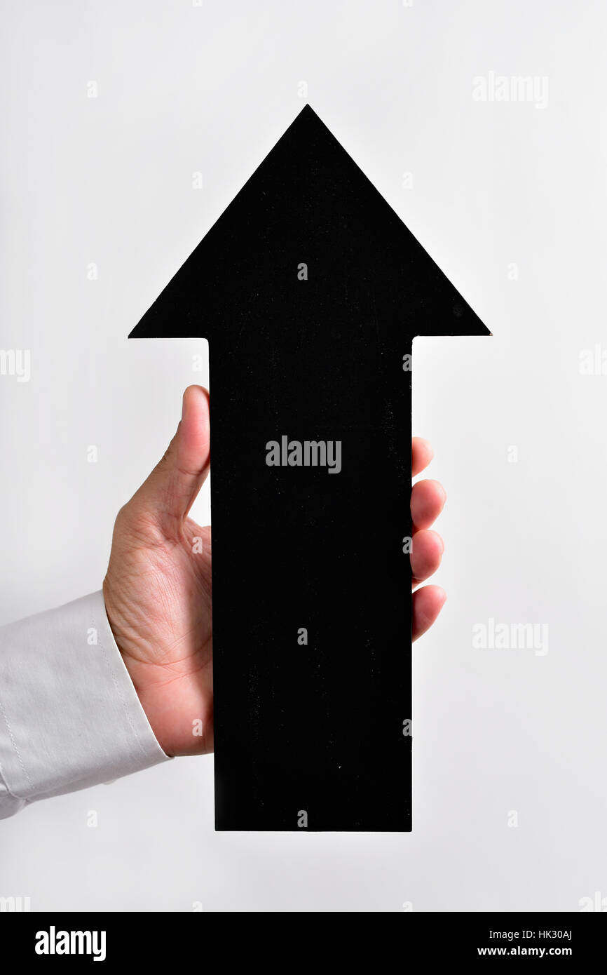 closeup of a young caucasian man holding a blank black arrow-shaped signboard pointing upwards - Stock Image