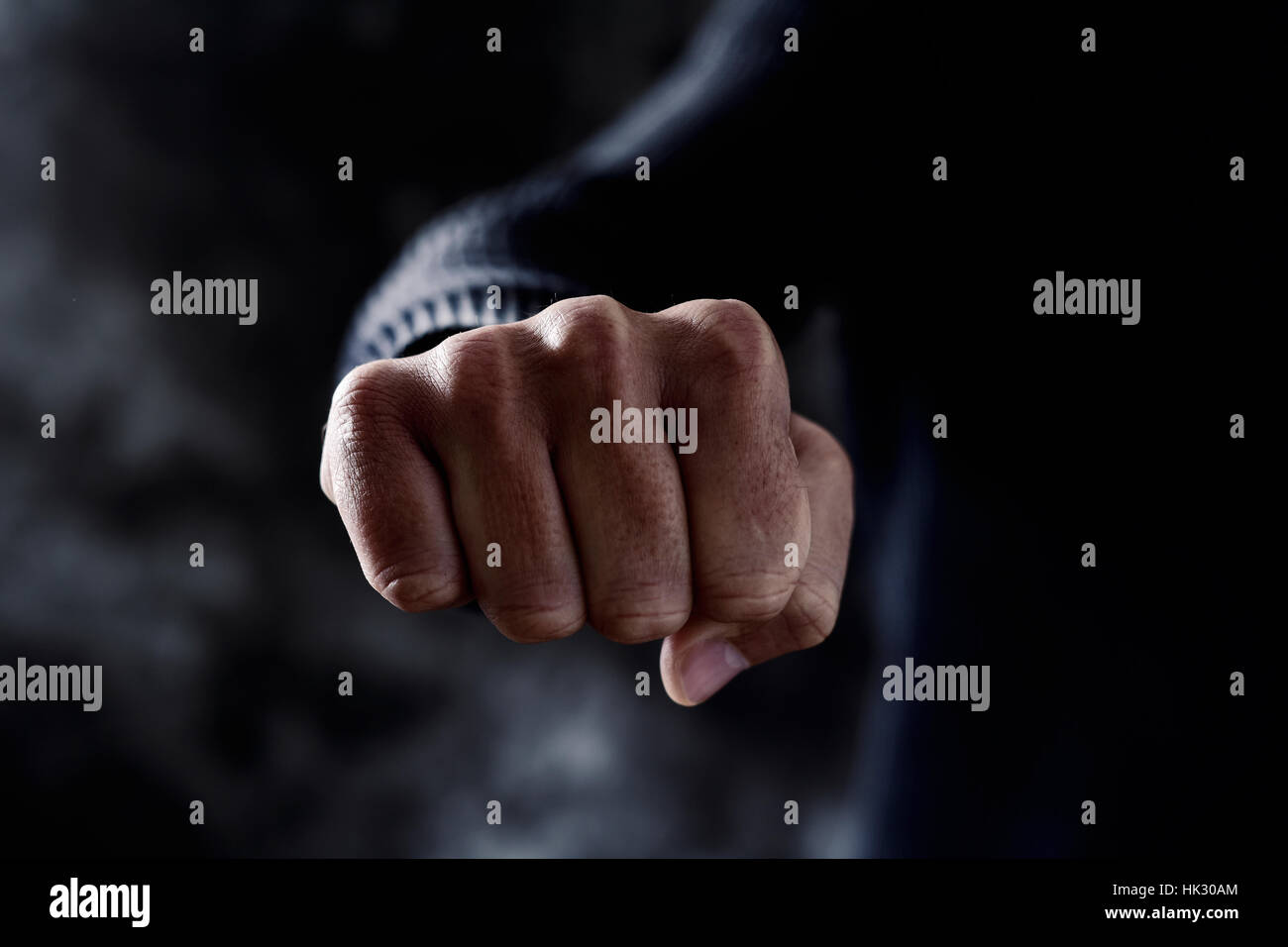 closeup of a young caucasian man in casual wear with a threatening gesture, with his fist clenched and pointing - Stock Image