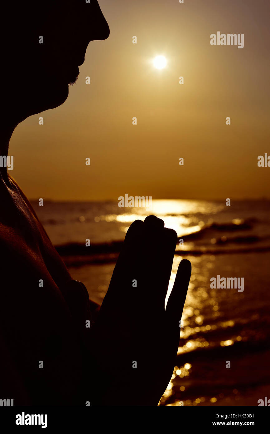the silhouette of a young man with his hands put together as prying in front of the sea in backlight - Stock Image