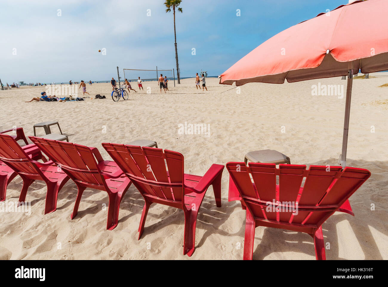 Five Red Plastic Adirondack Chairs And A Faded Red Umbrella Sitting On The  Sand At Venice