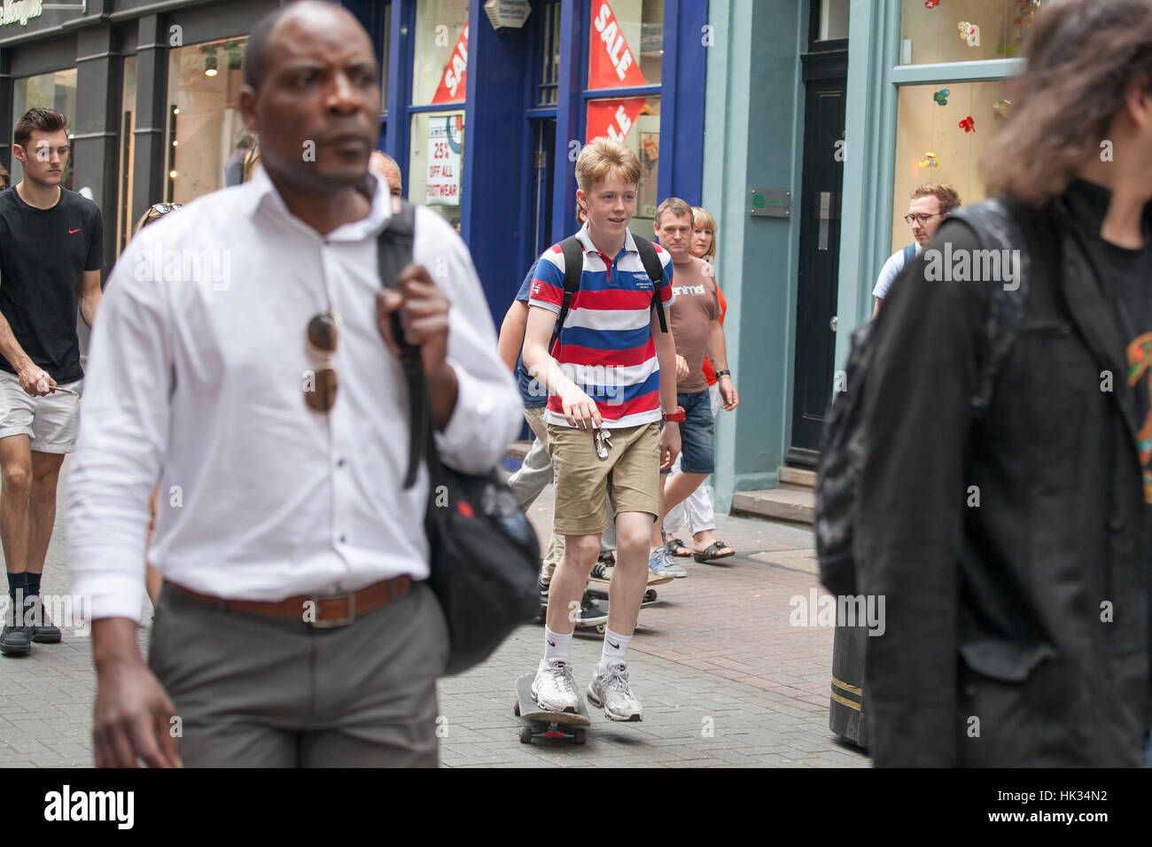 LONDON, ENGLAND - JULY 12, 2016 The boy in the striped T-shirt skating through the crowd in Carnaby street - Stock Image