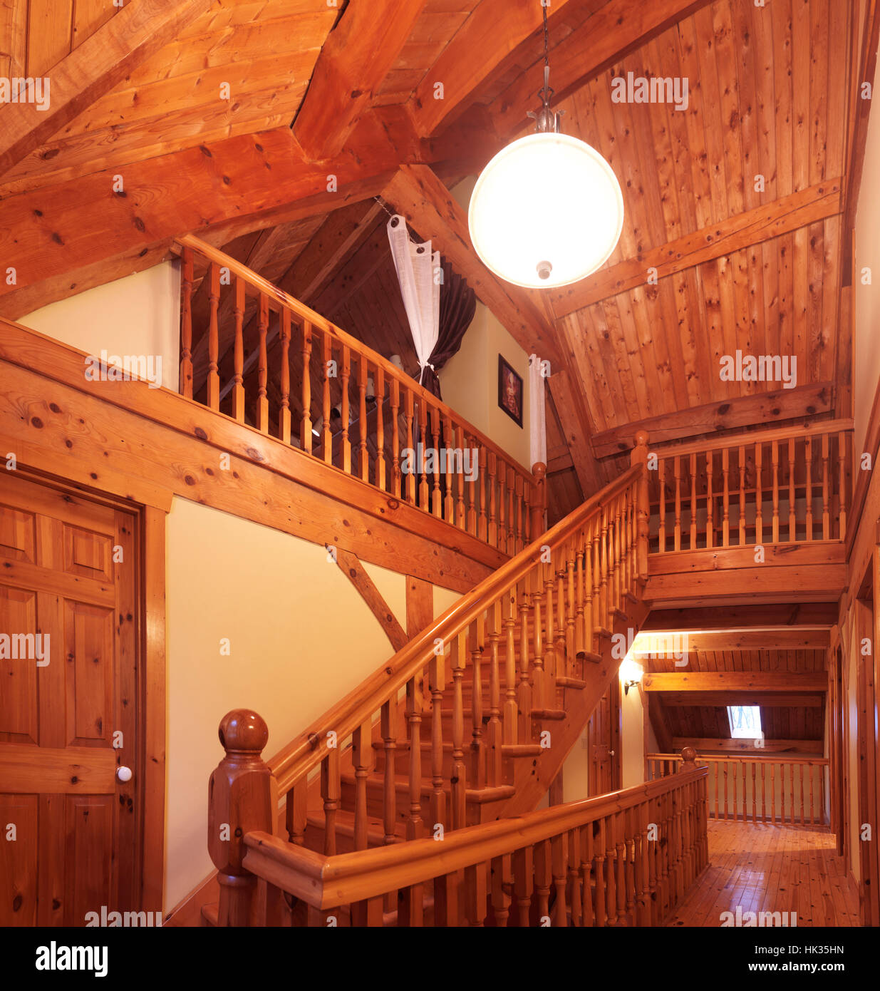Timber frame cottage style Canadian country house interior with a wooden staircase leading to the loft, Muskoka, - Stock Image