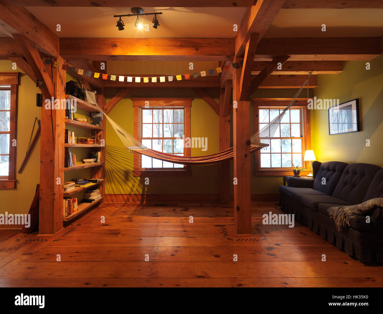 Lounge room with a hammock in a Canadian timber frame country house, interior with a lot of wood, Muskoka, Ontario, - Stock Image