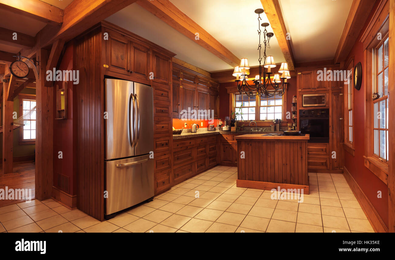 Spacious kitchen interior with lots of wood cabinets and elements in a timberframe Canadian country house in rustic - Stock Image