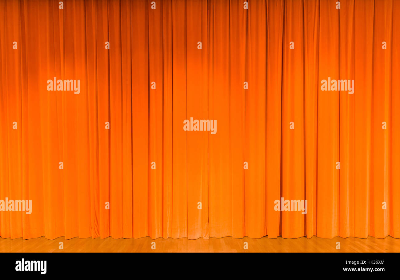 A curtain in orange color, covering a theater stage - Stock Image