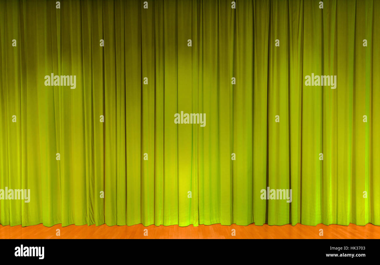 A curtain in green color, covering a theater stage - Stock Image