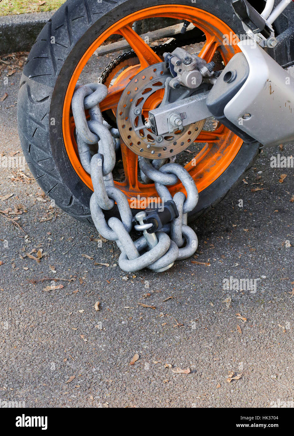 Motorcycle anti-theft chain with padlock security lock on rear wheel, protection against theft - Stock Image