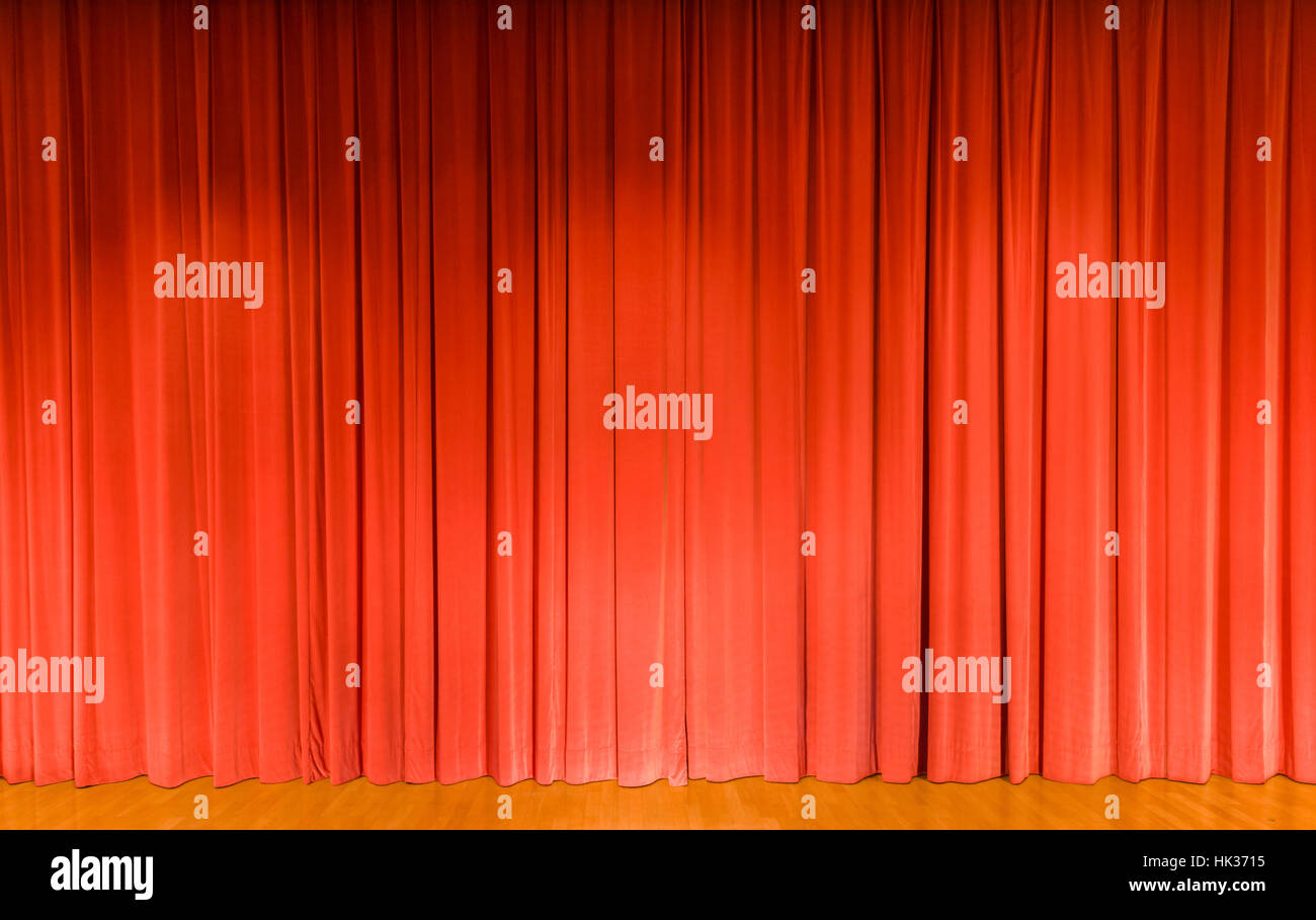 A curtain in light red color, covering a theater stage - Stock Image