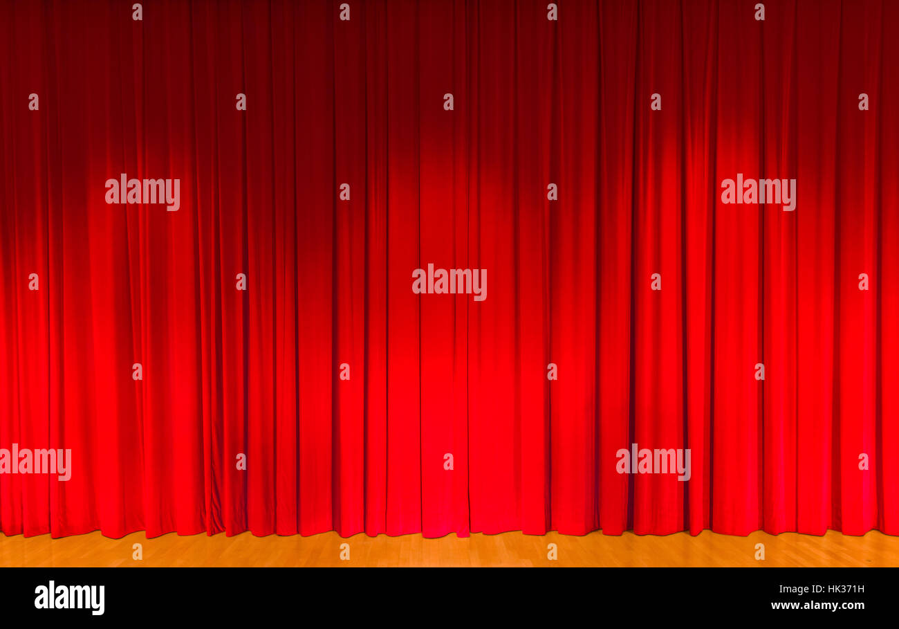 A curtain in dark red color, covering a theater stage - Stock Image