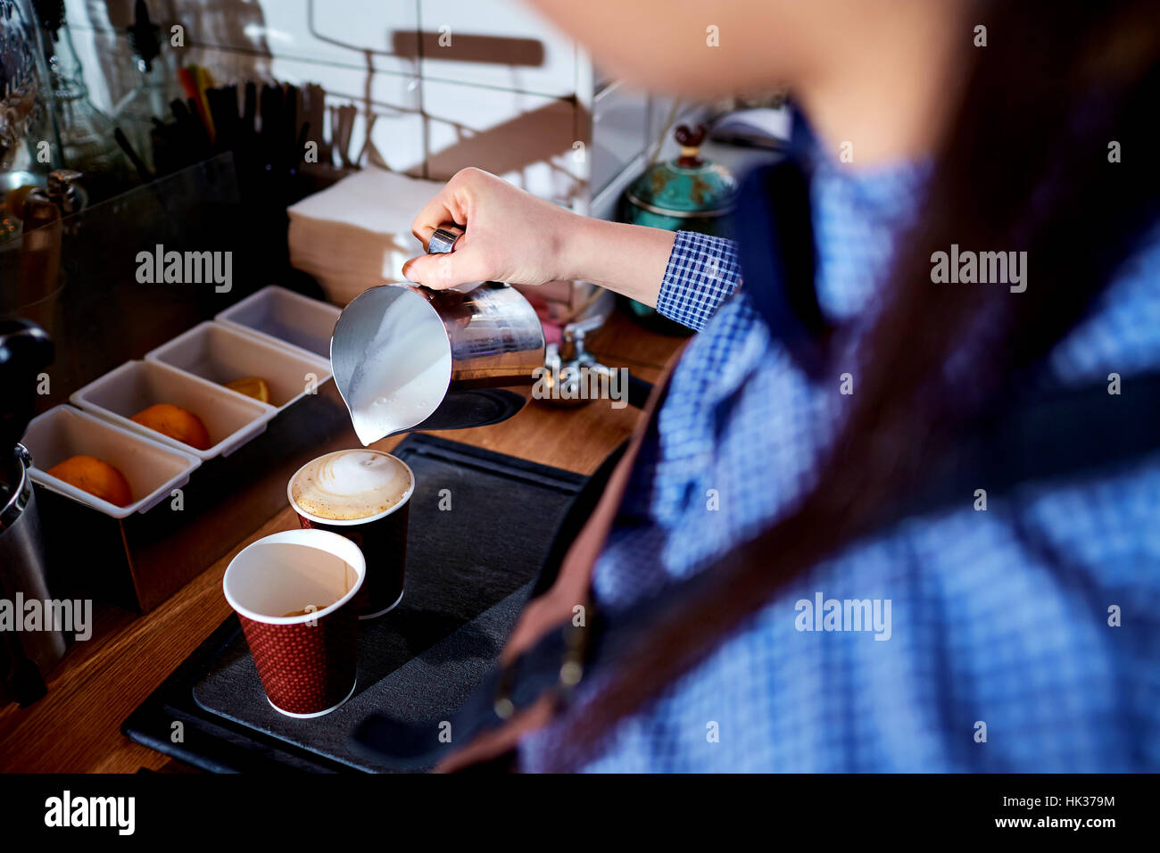 Bartender, barista pours coffee in a cup of cappuccino cafe bar - Stock Image