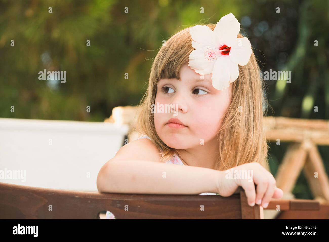 Thinking Cute Caucasian Little Girl With White Flower In Hair Stock