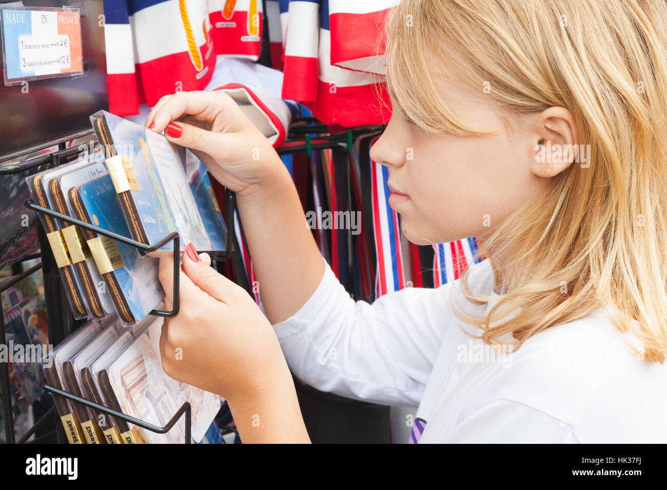 Paris, France - August 11, 2014: Blond Caucasian girl considers souvenirs in small street gift shop - Stock Image