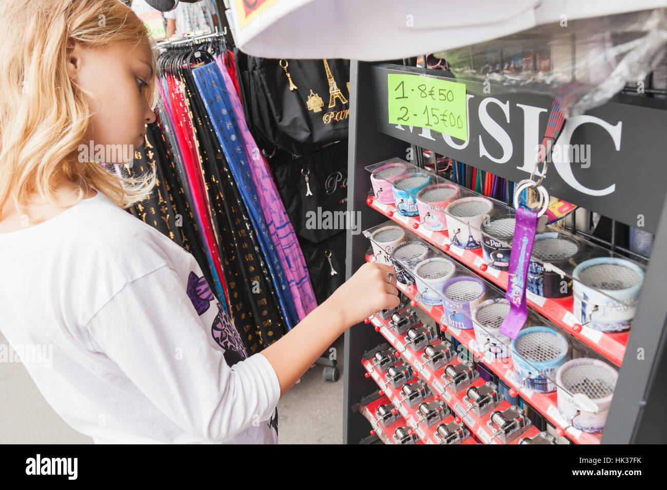 Paris, France - August 11, 2014: Blond Caucasian girl considers souvenirs in small street gift shop. Traditional - Stock Image