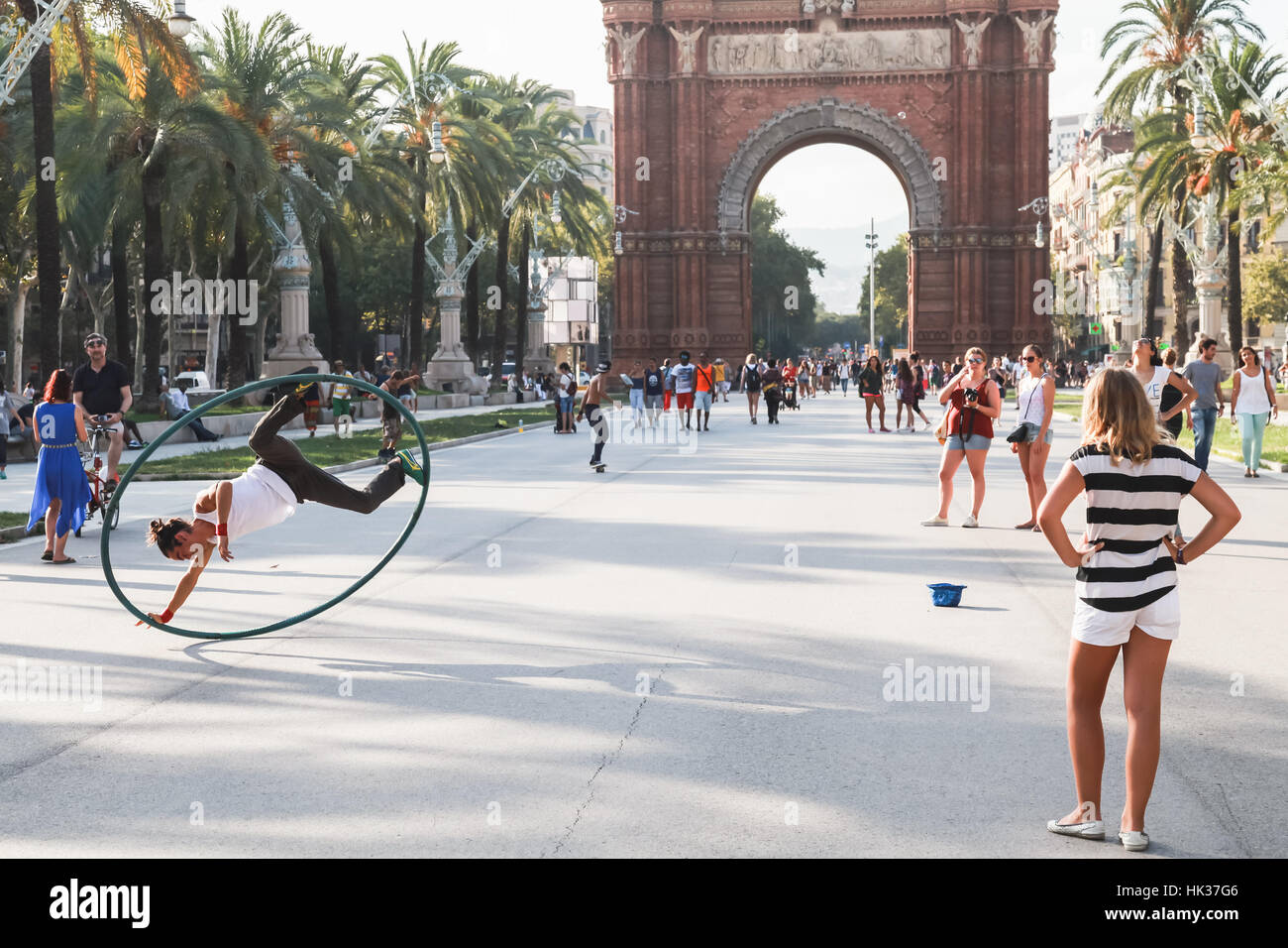 Barcelona, Spain - August 26, 2014: Acrobat with hoop makes performance in Ciutadella Park, Triumphal Arc on a background - Stock Image