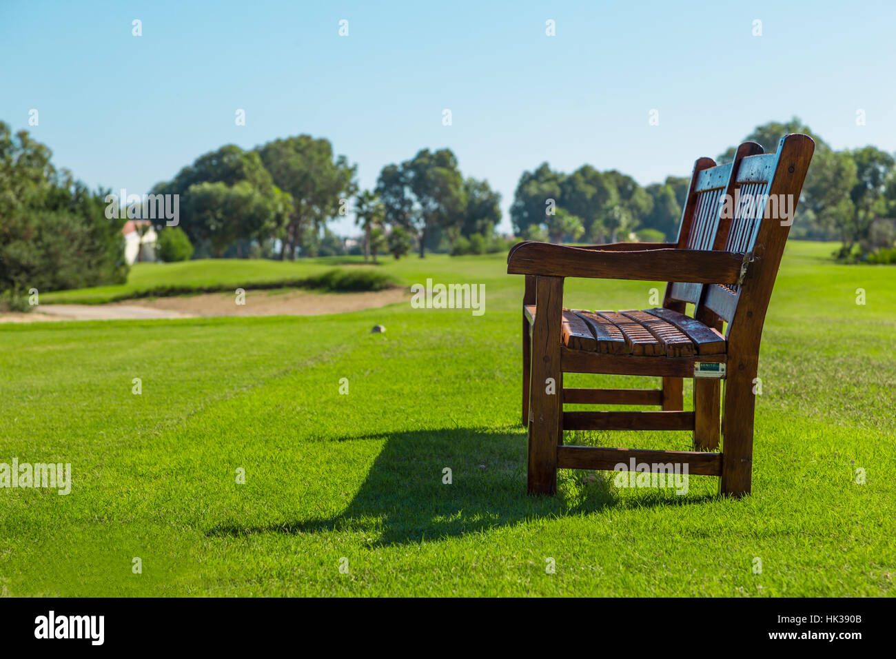 Wooden bench on a sunny day in golf courseStock Photo