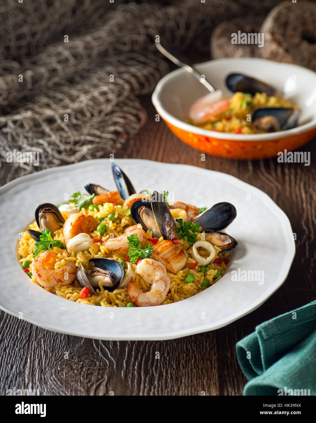 A bowl of delicious seafood and rice with shrimp, scallops, mussels, and calamari rings. - Stock Image